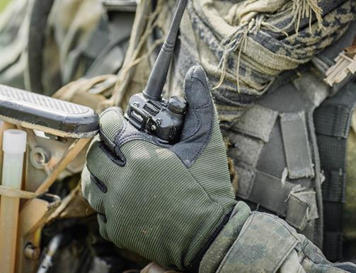 Camo Glove holding a walkie talkie