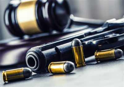 A court gavel with guns and bullets