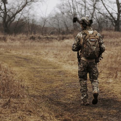 A soldier walking in a field alone