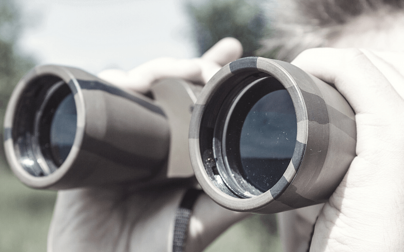 Military lookout, looking through binoculars