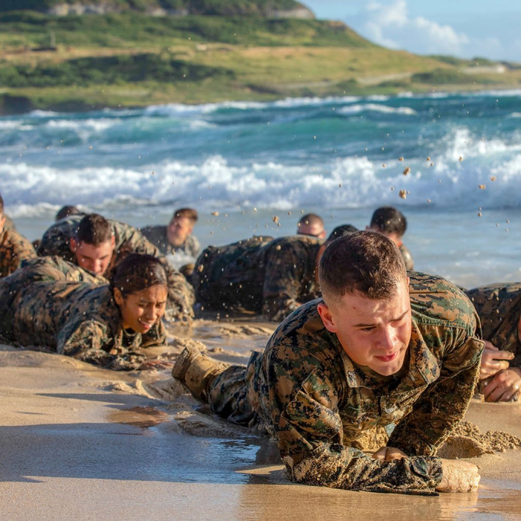 U.S. Marines attending Corporal's Course on Marine Corps Base Hawaii (MCBH), low crawl on Fort Hase Beach during a Small Unit Leadership Evaluation (SULE), Dec. 12, 2018. Corporal's Course is a Professional Military Education course designed to help corporals be prepared to be future sergeants by incorporating classroom instruction, physical fitness and Marine rifleman skills. The mission of the SULE is to challenge students to utilize the knowledge gained from the course through rigorous timed events that include land navigation, casualty evacuation and leading U.S. Marines. (U.S. Marine Corps photo by Sgt. Jesus Sepulveda Torres)