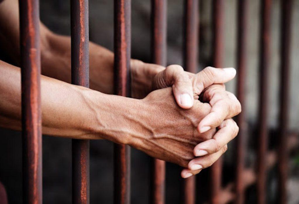 hands of prisoner in jail background.